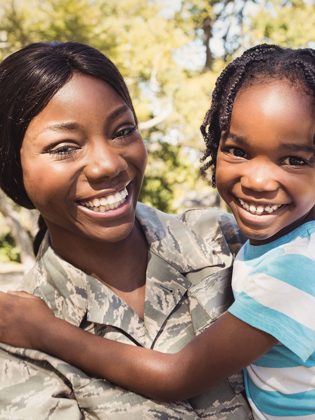 Military mom in fatigues holding young daughter in her arms