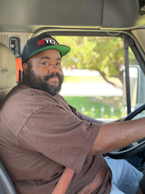 Driver wearing TCI baseball cap at the wheel