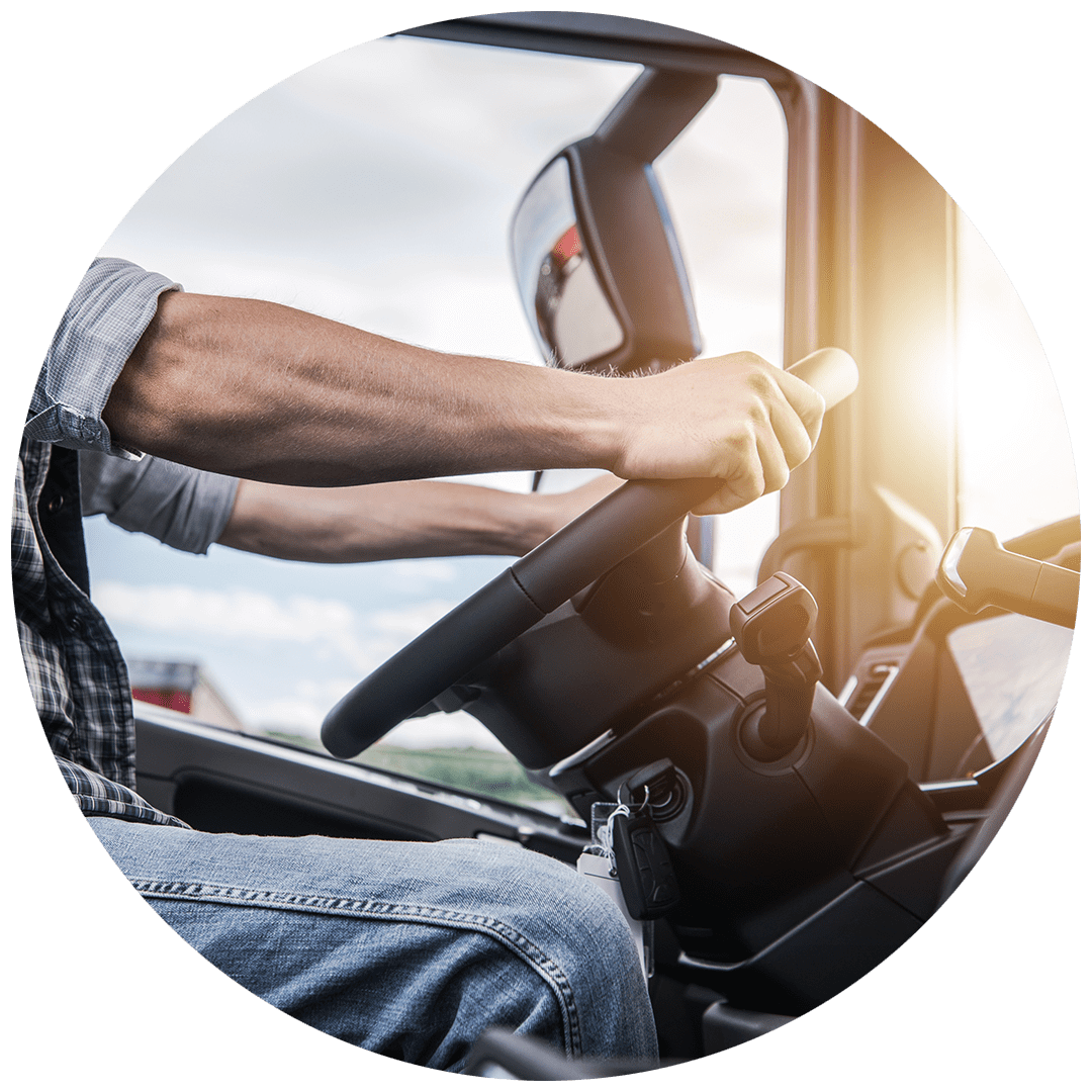 Close-up of man holding steering wheel in cab of truck